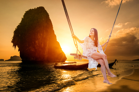 Beautiful woman sitting on a swing on the beach  in Krabi, Thailand Stock Photo