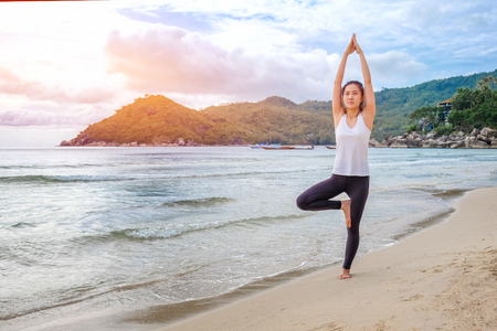 Young beautiful woman practicing yoga on the beach at sunrise