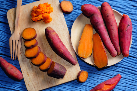 Sweet Potato on wooden cutting board with blue wood background Standard-Bild