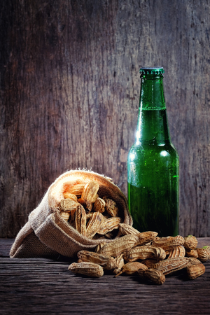 angle bar: Peanuts and greed beer bottle in wood background