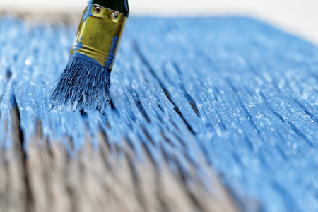 Paintbrush in hand and painting a wooden table