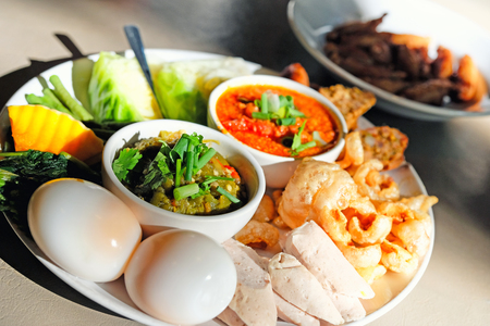 Thai food - Northern style red and green chilli dips with  northern thai spicy sausage (sai oua), streaky pork with crispy crackling and  vegetables Stock Photo