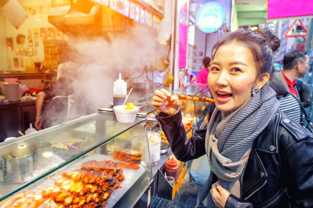 Chinese Asian young female model eating Grilled octopus on Street in Hong Kong Stockfoto