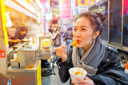 Chinese Asian young female model eating Chinese Steamed Dumpling on Street in Hong Kong Foto de archivo