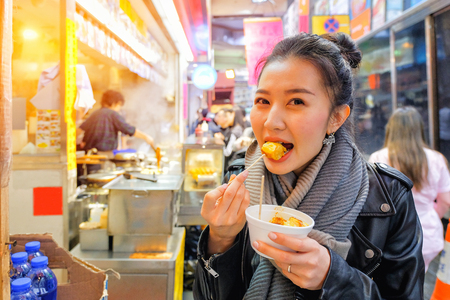 Chinese Asian young female model eating Chinese Steamed Dumpling on Street in Hong Kong 版權商用圖片