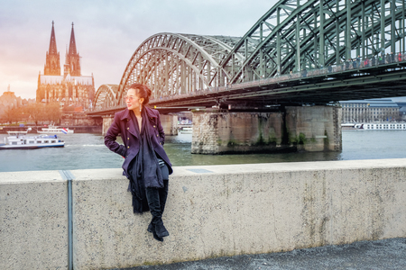 Yound beautiful woman sitting by the river with beautiful Cologne Cathedral in Germany