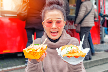 Young Woman Eating A  French Fries and salmon Street food in Germany