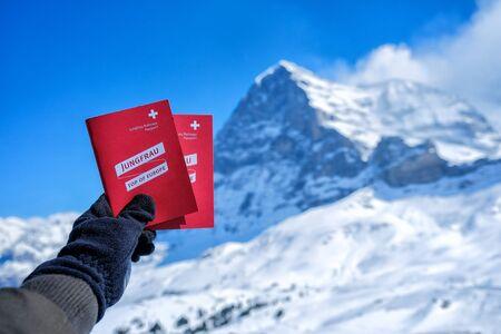 KLEINE SCHEIDEGG - 27 MARCH : Tourists see beautiful viewpoitn near Kleine Scheidegg station and showing Jungfraujoch red pass and snow mountain background at 27 March 2017, Switzerland Editorial