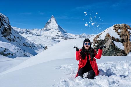 Young Woman Tourists playing snow in mountain Matterhorn peak, Zermatt, Switzerland.
