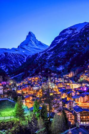 Beautiful view of old village in twilight time with Matterhorn peak background in Zermatt, Switzerland.