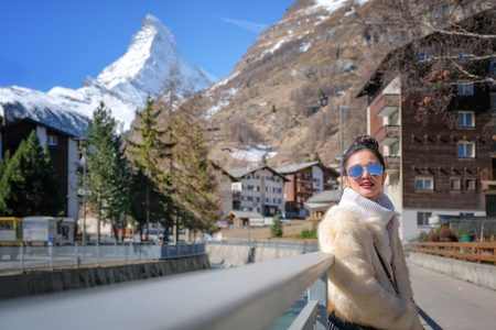 Young Woman Tourists see beautiful view of snow mountain Matterhorn in old town village in Zermatt, Switzerland. Stock Photo