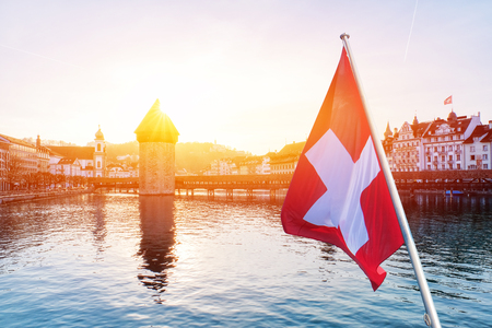 Panoramic view of city center of Lucerne with famous Chapel Bridge and lake Lucerne with Swiss flag, Switzerland