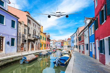 Front of real plane aircraft, on Burano Colorful house in Venice, Italy background