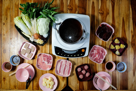 Thai style hot pot with delicious food ingredient on wood background