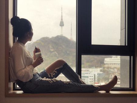 Young woman drinking coffee and looking out the window to see the view of Seoul Tower in the morning