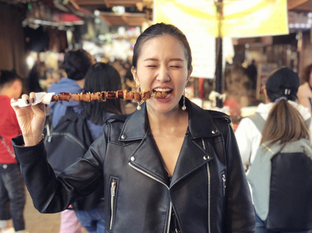 Young woman eating Steamed Octopus Legs at  at Myeong-dong street food, Seoul, South Korea Reklamní fotografie