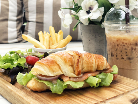Smoked salmon croissant sandwich served with coffee and french fried