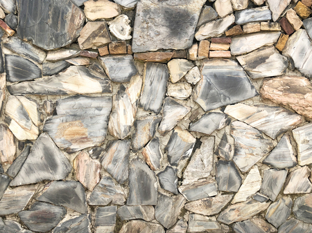 Rock wall pattern gray color of modern style design decorative uneven cracked real stone wall surface with cement