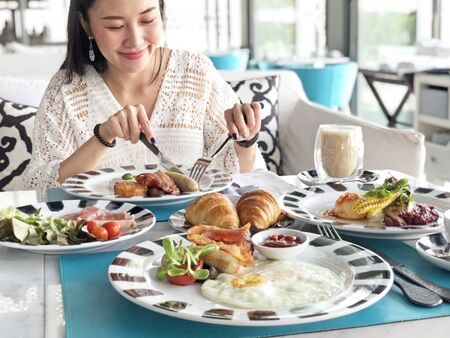 Young woman having healthy breakfast - fried egg, beans, salad, tomatoes, mushrooms, bacon and toast. Reklamní fotografie