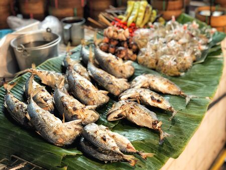 Fried mackerels on banana leaf Thai style bamboo basket for sell in street market.