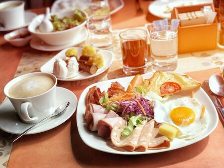 Delicious breakfast served with coffee, orange juice, egg, ham, salad, bacon rolls at the luxury hotel Stock Photo