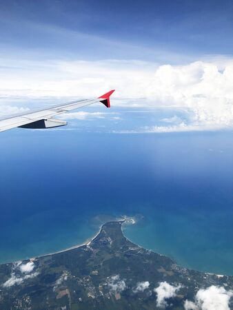 Wing of an airplane flying above the ocean