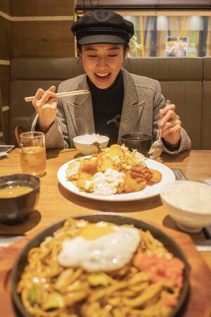 Beautiful asian woman enjoy eating Japanese food in restaurant Imagens