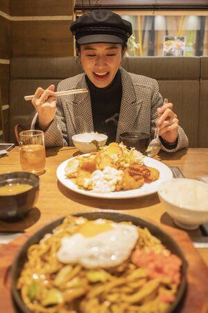Hermosa mujer asiática disfruta comiendo comida japonesa en el restaurante Foto de archivo