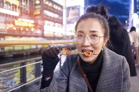 Young woman tourists enjoy eating street food in walking at street shopping center Dotonbori in Osaka, Japan.