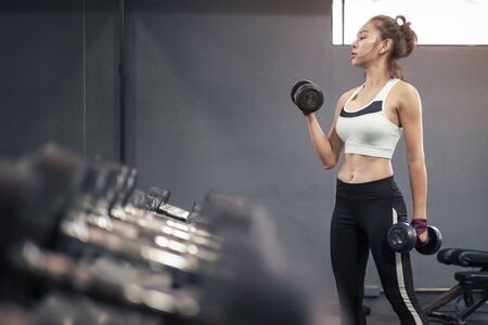 Young healthy woman lifting dumbbells in fitness gym Standard-Bild
