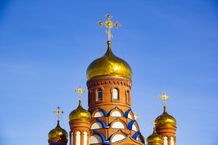beautiful gilded orthodox cross against the blue sky