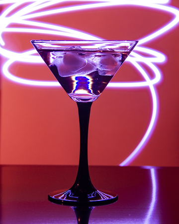 glass with coglass with cocktail and ice on a beautiful red background with cktail and ice on a beautiful background with neon stains