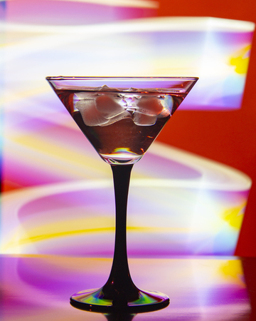glass with cocktail and ice on a beautiful background with neon colored lights
