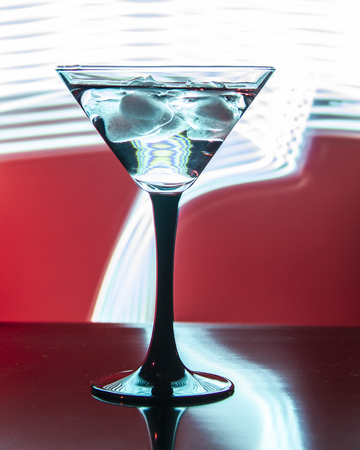 glass with cocktail and ice on a beautiful red background with neon