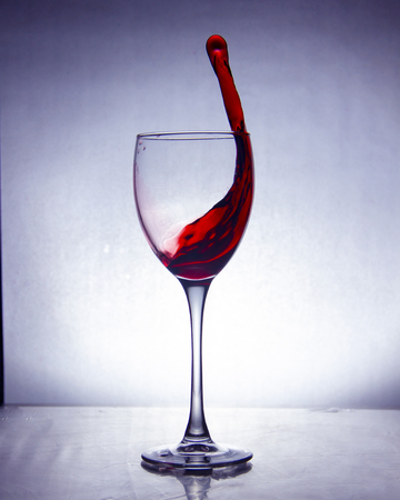 splash of the drink in the glass on the high leg on colored background Imagens - 123007451