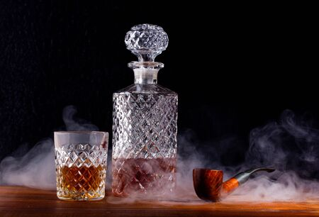 a fluted glass and decanter of whisky and a Smoking pipe on the table