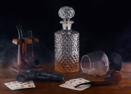 on the table are playing cards a pistol Smoking pipes with smoke and an overturned glass of whiskey Stock Photo