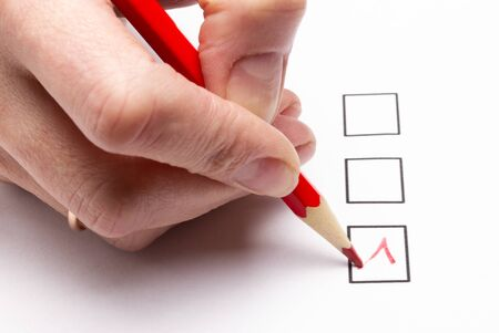 hand holding a red pencil makes a choice in the voting questionnaire Stock Photo