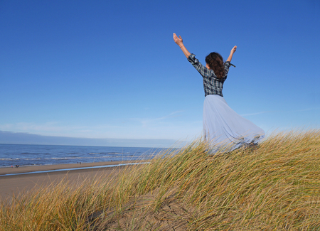 girl stands by the sea against the sky and hands up in a blue skirt and blue shirt. backs on the right side of the photo.