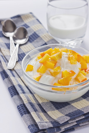 cream cottage cheese with sliced persimmons in a glass bowl photo