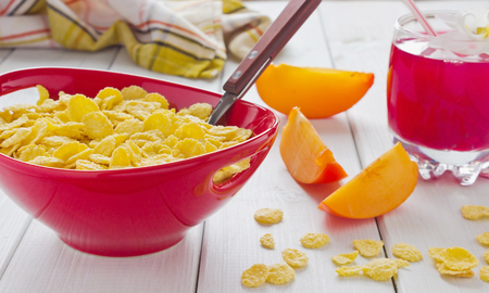 cornflakes, sliced fruit and a drink on the table photo