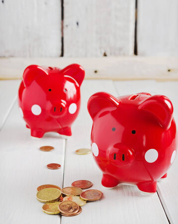 two red piggy bank and coins on the table