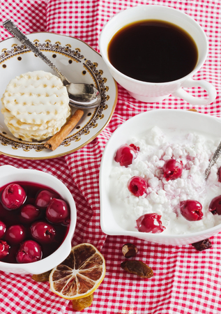 breakfast with cottage cheese and cherries on the table photo