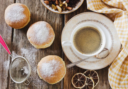 donuts with powdered sugar and a cup of coffee on a wooden background photo