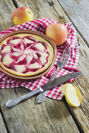 apple pie with jam and fresh apples on a wooden background photo