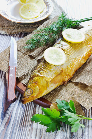whitefish: smoked fish with lemon, dill and parsley on a wooden background. whitefish Stock Photo