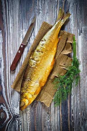 whitefish: smoked fish and dill on a wooden background. whitefish. Stock Photo