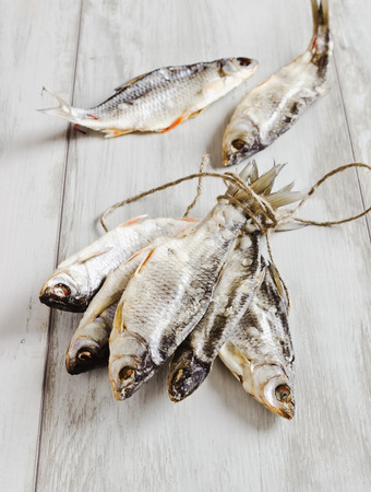 animal related: dried river fish tied with rope on a wooden background. selective focus
