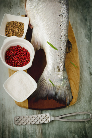 tail of salmon on a cutting board and various spices. selective focus.health and diet food photo