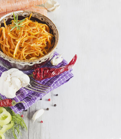 vitamin salad of grated carrots in a bowl and the ingredients on the table.health and diet food. copy space background photo